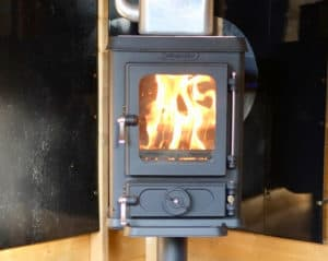 Shed small stove installation with a wall exit flue set up